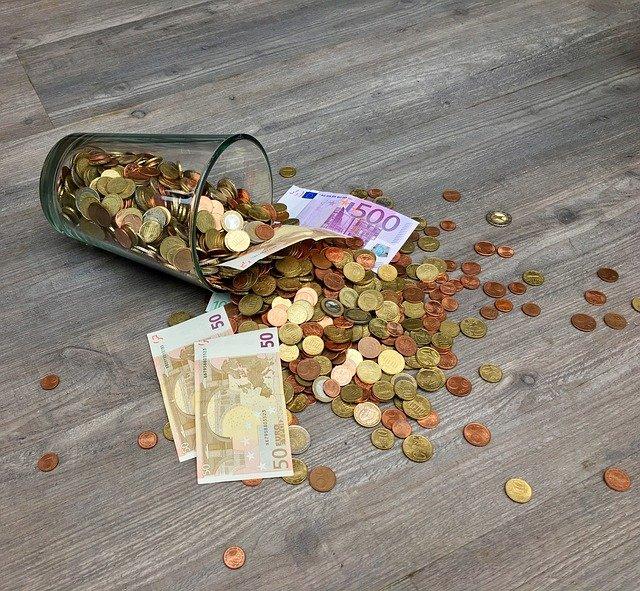 vysypaná sklenice s penězi