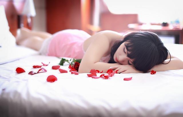 dívka na posteli s lístky růží