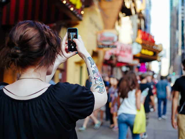 dívka s tetováním fotící rušnou ulici